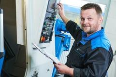Βιομηχανικός εργάτης που ενεργοποιεί cnc τη μηχανή στροφής στο μέταλλο που επεξεργάζεται τη βιομηχανία στη μηχανή Στοκ εικόνες με δικαίωμα ελεύθερης χρήσης