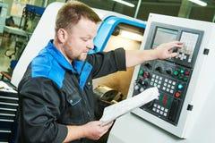 Βιομηχανικός εργάτης που ενεργοποιεί cnc τη μηχανή στροφής στο μέταλλο που επεξεργάζεται τη βιομηχανία στη μηχανή στοκ φωτογραφία