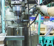 Βιομηχανικός εργάτης που τρυπά μια τρύπα σε έναν φραγμό μετάλλων με τρυπάνι Στοκ Φωτογραφία