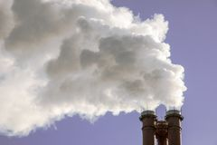 Βιομηχανικός καπνός σωλήνων εργοστασίων στον ήλιο στο μπλε ουρανό Προβλήματα οικολογίας Στοκ εικόνα με δικαίωμα ελεύθερης χρήσης