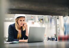 Βιομηχανικός μηχανικός γυναικών σε ένα εργοστάσιο που χρησιμοποιεί το lap-top και το smartphone στοκ εικόνα με δικαίωμα ελεύθερης χρήσης