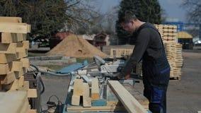 Βιομηχανικός νέος εργαζόμενος ξυλουργών στην ειδική ομοιόμορφη χρησιμοποιώντας ξύλινη τέμνουσα μηχανή απόθεμα βίντεο