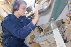 Βιομηχανικός ξυλουργός που χρησιμοποιεί το ηλεκτρονικό πριόνι Στοκ εικόνες με δικαίωμα ελεύθερης χρήσης