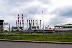 Βιομηχανικό αστικό τοπίο Τραίνο και καπνοδόχοι στο υπόβαθρο ενός θυελλώδους ουρανού στοκ φωτογραφία