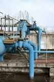 Βιομηχανικό διάστημα με τα μέρη των σωλήνων και των ανακοινώσεων σχετικά με ένα υπόβαθρο του μπλε ουρανού παλαιό εργοστάσιο επεξε Στοκ Εικόνες