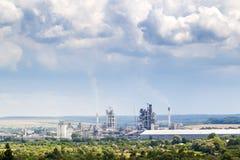 Βιομηχανικό εργοστάσιο τσιμέντου με τους σωλήνες που καπνίζουν και τα αυξομειούμενα σύννεφα αβ Στοκ Εικόνα