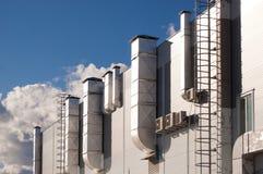 Βιομηχανικό κτήριο με τους σωλήνες εξαερισμού και τα κλιματιστικά μηχανήματα Στοκ φωτογραφία με δικαίωμα ελεύθερης χρήσης
