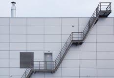 Βιομηχανικό κλιμακοστάσιο στη σύγχρονη πρόσοψη κεραμιδιών χάλυβα Στοκ Φωτογραφίες