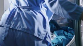 Βιομηχανικό ξηρότερο πλυντήριο πλύση μηχανών ενδυμάτων Εργαζόμενος που κάνει το πλυντήριο φιλμ μικρού μήκους