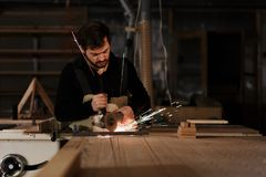 Βιομηχανικό τέμνον μέταλλο εργαζομένων ξυλουργών με πολλούς αιχμηρούς σπινθήρες σε έναν πάγκο εργασίας σε ένα εργαστήριο ξυλουργι στοκ εικόνες με δικαίωμα ελεύθερης χρήσης