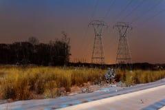 Βιομηχανικό τοπίο - φωτισμένος σιδηροδρομικός σταθμός μέχρι τη χειμερινή νύχτα με τις χιονοπτώσεις Στοκ εικόνες με δικαίωμα ελεύθερης χρήσης