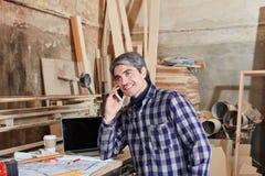 Βιοτέχνης με το τηλέφωνο κυττάρων Στοκ εικόνα με δικαίωμα ελεύθερης χρήσης