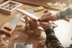 Βιοτέχνης που χτίζει ένα ξύλινο αεροπλάνο παιχνιδιών Στοκ Εικόνες