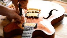 Βιοτέχνης Luthier που εργάζεται σε μια ηλεκτρική κιθάρα τζαζ στον εργασιακό χώρο απόθεμα βίντεο