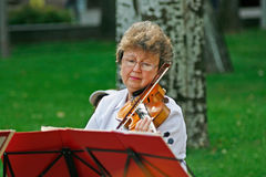 Βιολί παιχνιδιού ηλικιωμένων γυναικών στην οδό στην ημέρα πόλεων στο Βόλγκογκραντ στοκ φωτογραφίες