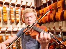 Βιολιστής αγοριών που παίζει ένα βιολί στο Music Store Στοκ φωτογραφία με δικαίωμα ελεύθερης χρήσης