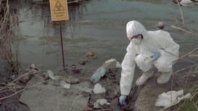 Βιο-κίνδυνος στη φύση, hazmat φαρμακοποιός στο προστατευτικό κοστούμι που παίρνει τη μολυσμένη δειγματοληψία ύδατος στους σωλήνες απόθεμα βίντεο