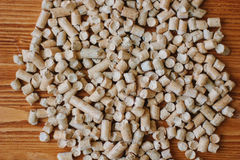 Βιολογικά καύσιμα - μικροί ξύλινοι σβόλοι πέρα από τον ξύλινο πίνακα στοκ φωτογραφία