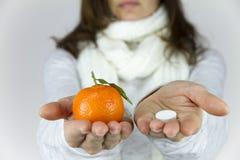Βιταμίνες από τα φρούτα ή τα φάρμακα; Μια άρρωστη νέα γυναίκα με ένα μαντίλι στο λαιμό της παρουσιάζει ένα μανταρίνι σε την δεξιά στοκ φωτογραφία