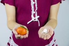 Βιταμίνες από τα φρούτα ή τα φάρμακα; Μια νέα γυναίκα burgundy στις πυτζάμες παρουσιάζει ένα μανταρίνι σε την δεξιά και τη aspiri στοκ εικόνα