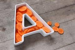 Βιταμίνη Α στην έννοια τροφίμων Πιάτο με μορφή του γράμματος Α με τα τεμαχισμένα φρέσκα καρότα Στοκ φωτογραφία με δικαίωμα ελεύθερης χρήσης
