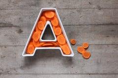 Βιταμίνη Α στην έννοια τροφίμων Πιάτο με μορφή του γράμματος Α με τα τεμαχισμένα φρέσκα καρότα στο ξύλινο υπόβαθρο Επίπεδος βάλτε Στοκ φωτογραφίες με δικαίωμα ελεύθερης χρήσης