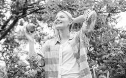 Βιταμίνη και να κάνει δίαιτα τρόφιμα οπωρώνας, κορίτσι κηπουρών στον κήπο μήλων Ευτυχής γυναίκα που τρώει το μήλο r πείνα στοκ εικόνα με δικαίωμα ελεύθερης χρήσης