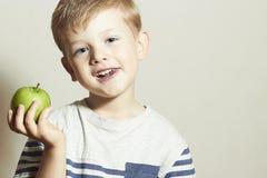 βιταμίνη Χαμογελώντας παιδί με το μήλο Μικρό παιδί με το πράσινο μήλο μακρο λευκό στούντιο υγείας τροφίμων νιφάδων καλαμποκιού αν Στοκ Εικόνες