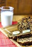 Βλασταημένος του ενιαίου ψωμιού μπανανών με τις φέτες του ψωμιού με το ποτήρι του γάλακτος Στοκ Εικόνα