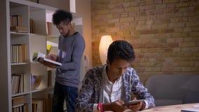 Βλαστός κινηματογραφήσεων σε πρώτο πλάνο δύο πολιτιστικά διαφορετικών σπουδαστών που μαθαίνουν στη σχολική βιβλιοθήκη στο εσωτερι απόθεμα βίντεο