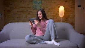 Βλαστός κινηματογραφήσεων σε πρώτο πλάνο νέο όμορφο καυκάσιο θηλυκό brunette στη συνεδρίαση ταμπλετών στον καναπέ σε ένα άνετο δι απόθεμα βίντεο