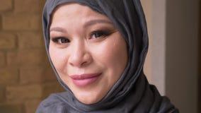 Βλαστός κινηματογραφήσεων σε πρώτο πλάνο της ενήλικης μουσουλμανικής επιτυχούς γυναίκας υπάλληλος στο hijab που εξετάζει τη κάμερ φιλμ μικρού μήκους