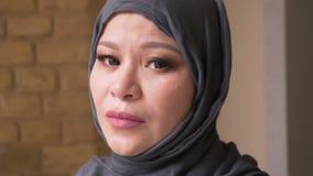 Βλαστός κινηματογραφήσεων σε πρώτο πλάνο της ενήλικης μουσουλμανικής γυναίκας υπάλληλος στο hijab που εξετάζει τη κάμερα σκεπτικά φιλμ μικρού μήκους