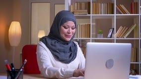 Βλαστός κινηματογραφήσεων σε πρώτο πλάνο της ενήλικης μουσουλμανικής δακτυλογράφησης επιχειρηματιών στο lap-top και του χαμόγελου φιλμ μικρού μήκους