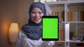Βλαστός κινηματογραφήσεων σε πρώτο πλάνο της ενήλικης μουσουλμανικής γυναίκας υπάλληλος στο hijab χρησιμοποιώντας την ταμπλέτα κα φιλμ μικρού μήκους