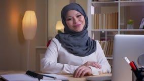 Βλαστός κινηματογραφήσεων σε πρώτο πλάνο της ενήλικης μουσουλμανικής γυναίκας υπάλληλος στο hijab που χαμογελά ευτυχώς και που κρ απόθεμα βίντεο