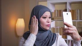 Βλαστός κινηματογραφήσεων σε πρώτο πλάνο της ενήλικης μουσουλμανικής γυναίκας υπάλληλος στο hijab που παίρνει selfies στο τηλέφων απόθεμα βίντεο