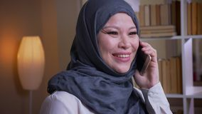 Βλαστός κινηματογραφήσεων σε πρώτο πλάνο της ενήλικης μουσουλμανικής γυναίκας υπάλληλος στο hijab που μιλά ευτυχώς στο τηλέφωνο σ απόθεμα βίντεο
