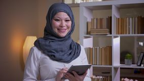 Βλαστός κινηματογραφήσεων σε πρώτο πλάνο της ενήλικης μουσουλμανικής γυναίκας υπάλληλος στο hijab που χρησιμοποιεί την ταμπλέτα π φιλμ μικρού μήκους