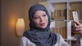 Βλαστός κινηματογραφήσεων σε πρώτο πλάνο της ενήλικης μουσουλμανικής γυναίκας υπάλληλος στο hijab που παίρνει selfies στο τηλέφων φιλμ μικρού μήκους