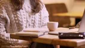 Βλαστός κινηματογραφήσεων σε πρώτο πλάνο της επιχειρηματία σε μια διαδικασία σε ένα σημειωματάριο που παρουσιάζεται έναν καφέ στο φιλμ μικρού μήκους