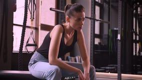 Βλαστός κινηματογραφήσεων σε πρώτο πλάνο της νέας ελκυστικής θηλυκής συνεδρίασης αθλητών στη γυμναστική sportswear που εξετάζει τ απόθεμα βίντεο