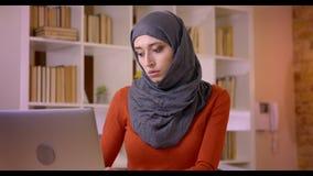 Βλαστός κινηματογραφήσεων σε πρώτο πλάνο της νέας ελκυστικής μουσουλμανικής γυναίκας υπάλληλος στη δακτυλογράφηση hijab στο lap-t απόθεμα βίντεο