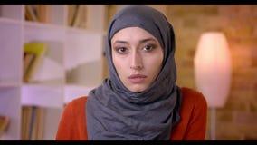 Βλαστός κινηματογραφήσεων σε πρώτο πλάνο της νέας ελκυστικής μουσουλμανικής γυναίκας υπάλληλος που εξετάζει τη κάμερα στον εργασι απόθεμα βίντεο