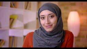 Βλαστός κινηματογραφήσεων σε πρώτο πλάνο της νέας ελκυστικής μουσουλμανικής γυναίκας υπάλληλος που εξετάζει τη κάμερα και που χαμ απόθεμα βίντεο