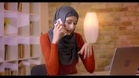 Βλαστός κινηματογραφήσεων σε πρώτο πλάνο της νέας ελκυστικής μουσουλμανικής γυναίκας υπάλληλος στο hijab που έχει ένα τηλεφώνημα  απόθεμα βίντεο