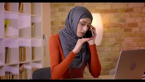 Βλαστός κινηματογραφήσεων σε πρώτο πλάνο της νέας ελκυστικής μουσουλμανικής γυναίκας υπάλληλος στο hijab που έχει μια συνομιλία σ απόθεμα βίντεο