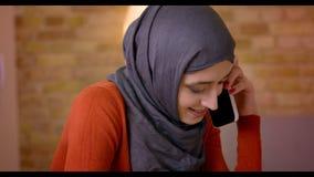 Βλαστός κινηματογραφήσεων σε πρώτο πλάνο της νέας ελκυστικής μουσουλμανικής γυναίκας υπάλληλος στο hijab που μιλά στο τηλέφωνο κα φιλμ μικρού μήκους