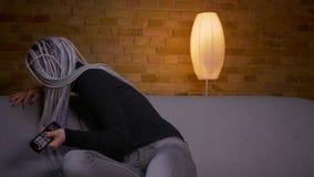 Βλαστός κινηματογραφήσεων σε πρώτο πλάνο της νέας ελκυστικής καυκάσιας συνεδρίασης TV προσοχής hipster θηλυκής στον καναπέ στο εσ απόθεμα βίντεο