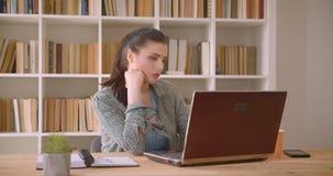 Βλαστός κινηματογραφήσεων σε πρώτο πλάνο της νέας καυκάσιας επιχειρηματία που χρησιμοποιεί το lap-top στο γραφείο βιβλιοθηκών στο απόθεμα βίντεο